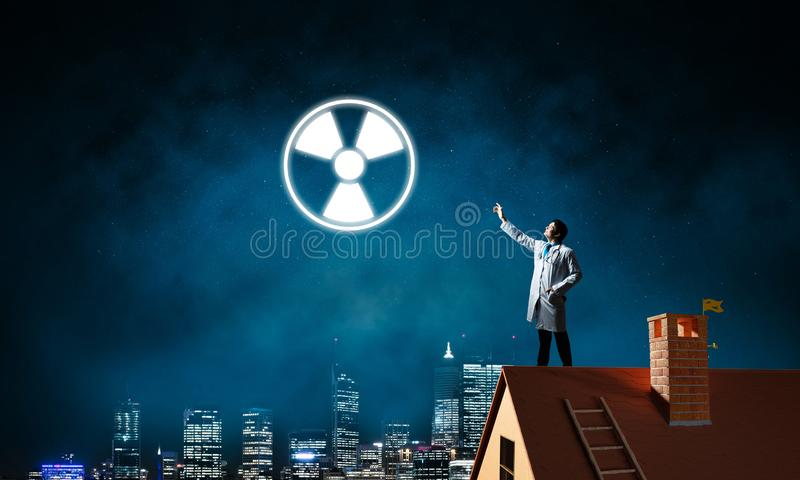Medical industry and radioactive materials. Young medical industry employee standing on brick house roof and interracting with glowing radioactive symbol with royalty free stock images