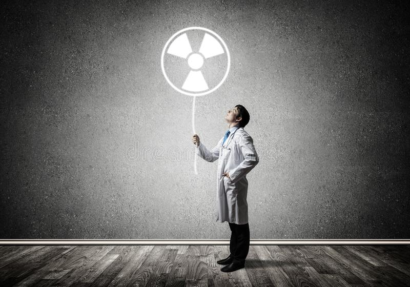 Medical industry and radioactive materials. Young medical industry employee standing inside empty room and interracting with glowing radioactive symbol with gray royalty free stock image
