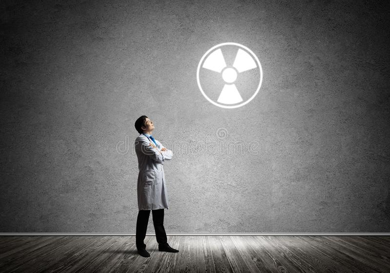 Medical industry and radioactive materials. Young medical industry employee standing inside empty room and interracting with glowing radioactive symbol with gray stock photography