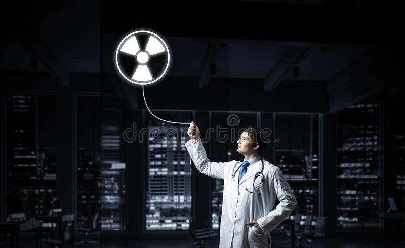 Medical industry and radioactive materials. Young medical industry employee interracting with glowing radioactive symbol while standing against night cityscape stock photo