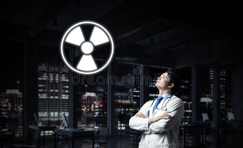 Medical industry and radioactive materials. Young medical industry employee interracting with glowing radioactive symbol while standing against night cityscape stock photos