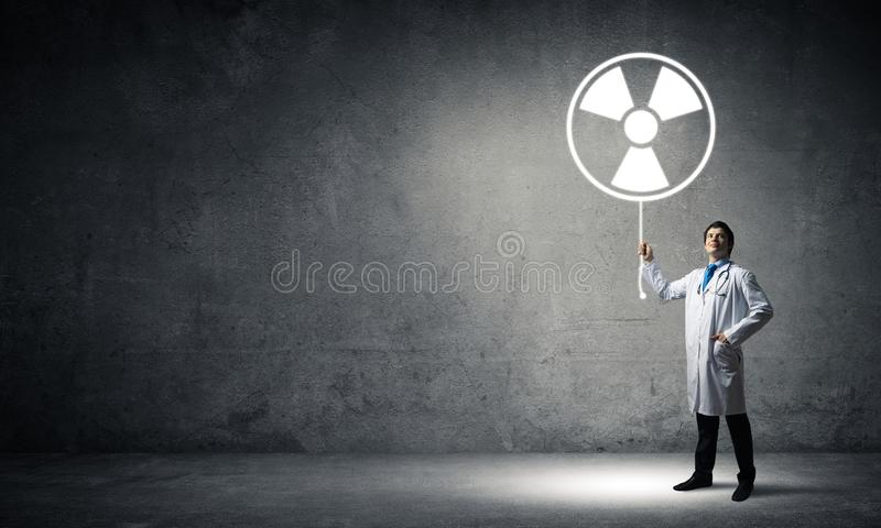 Medical industry and radioactive materials. Young medical industry employee standing inside empty room and interracting with glowing radioactive symbol with gray stock photos