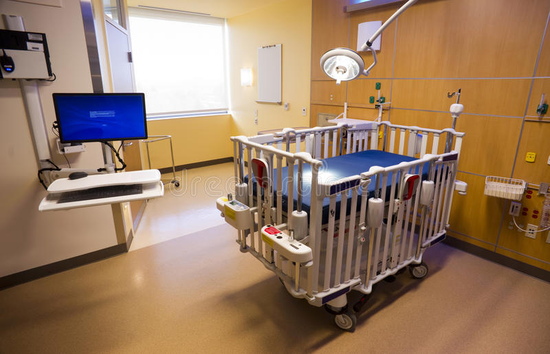 Medical Inspection Light Shines Down Bed Childrens Hospital Room. Medical Inspection Light Shines Down on Bed Next to Computer Terminal Childrens Hospital Room stock image