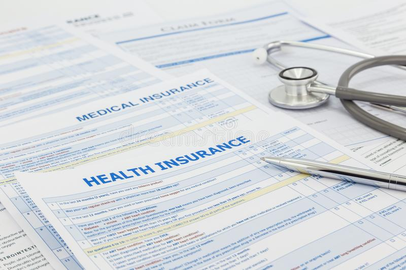 Medical insurance application and legal contract. Medical insurance application, silver pen and stethoscope. Legal law contract and health insurance concepts royalty free stock photo