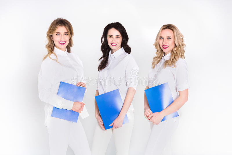 Medical internship, women in white uniform. Medical internship. Happy young women in white uniform posing on isolated studio background, copy space stock photography