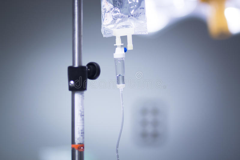 Medical iv drip in hospital. Medical intravenous IV drip in hospital used to replace liquids in patients in surgery in operating emergency room during operations royalty free stock image