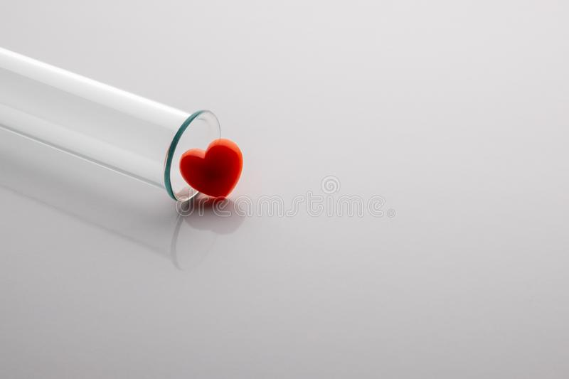 A medical or laboratory glass test tube with a red heart lies on a white table. Close-up. Copy space royalty free stock photography