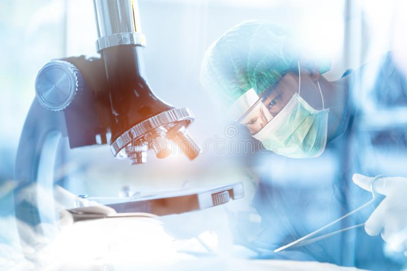 Medical laboratory microscope with Asian surgery doctor in operation room. Medical and healthcare research concept. Clinic and. Hospital theme. Double exposure stock photography