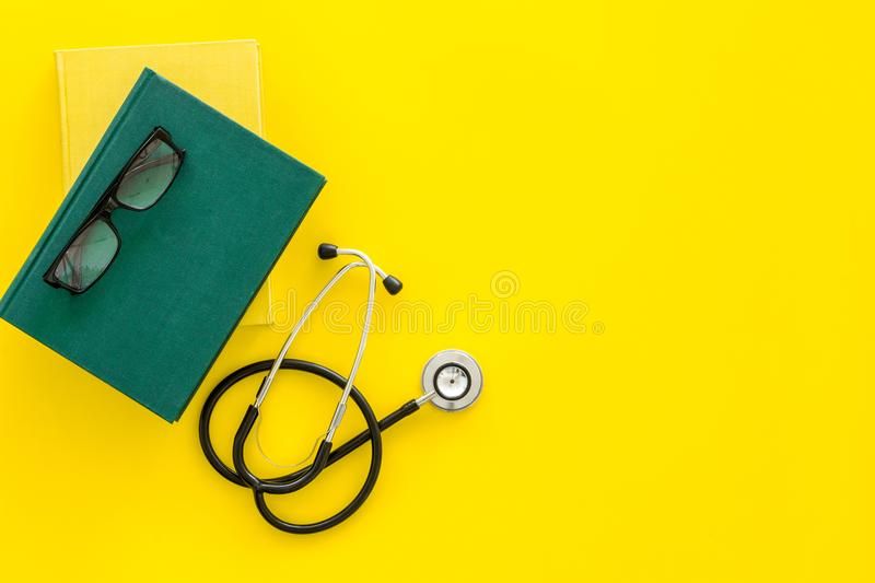 Medical literature. Stethoscope near book and glasses on yellow background top view copy space. Medical literature. Stethoscope near book and glasses on yellow stock photos