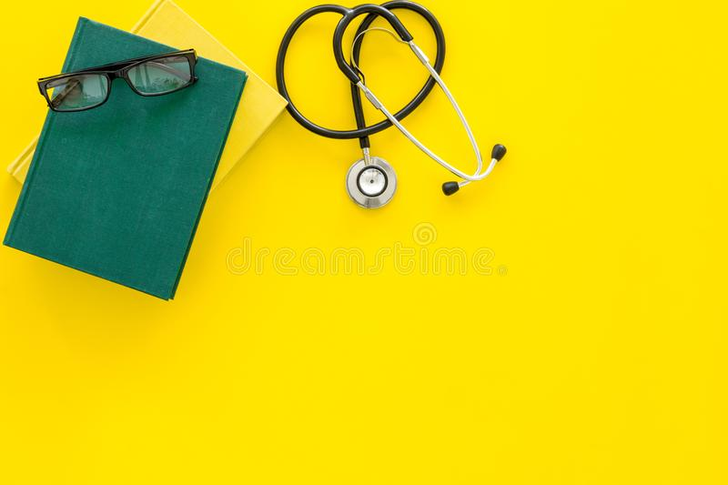 Medical literature. Stethoscope near book and glasses on yellow background top view copy space. Medical literature. Stethoscope near book and glasses on yellow stock photography