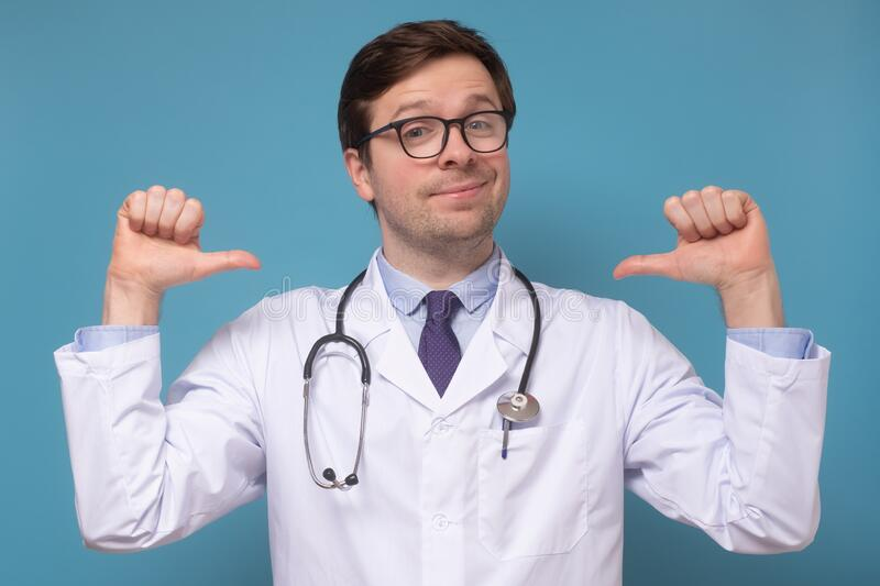 Medical man intern or doctor feeling proud and self assured triumphing, being winner pointing at himself. Caucasian young medical man intern or doctor feeling royalty free stock photo