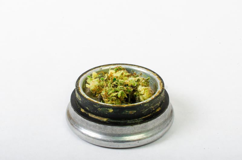 Medical marijuana ground up and ready to roll. With a steel bud buster. stock photo