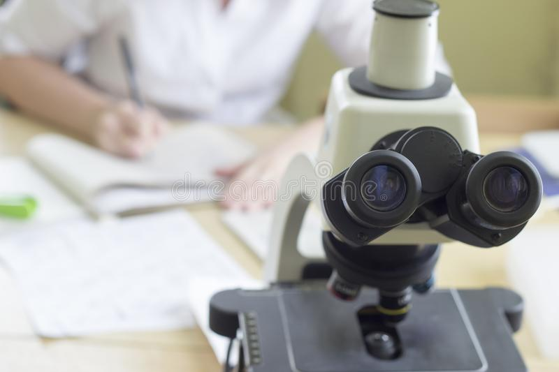 Medical microscope, in the background a doctor filling out test results medical stock image