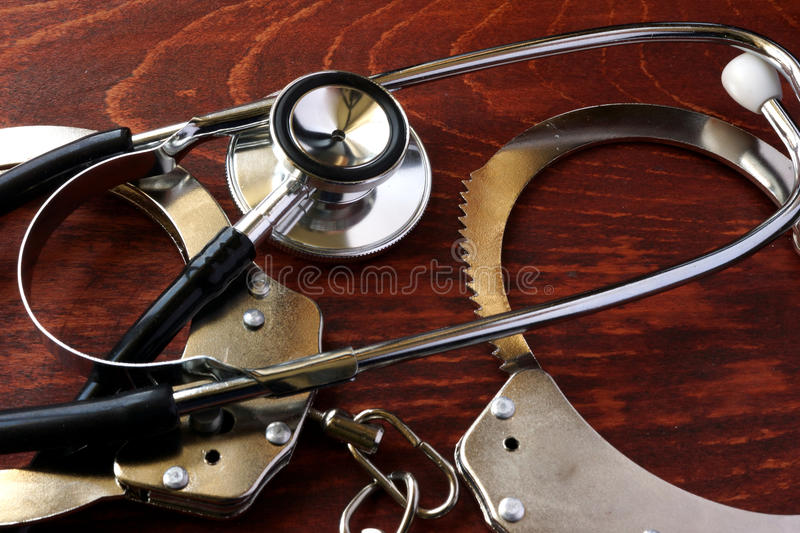 Medical negligence concept. Stethoscope and handcuffs stock images