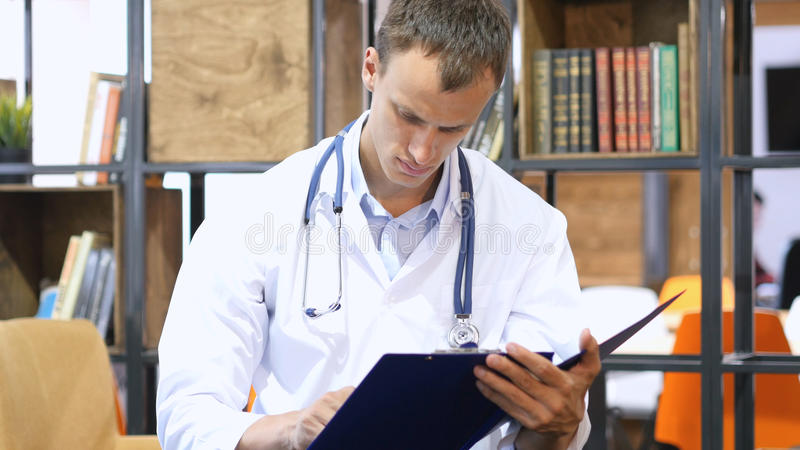 Medical office - male doctor looking down reading documents thinking. High quality royalty free stock photography