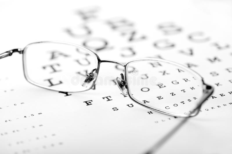 Medical optics concept. With glasses on eye chart - monochrome stock images