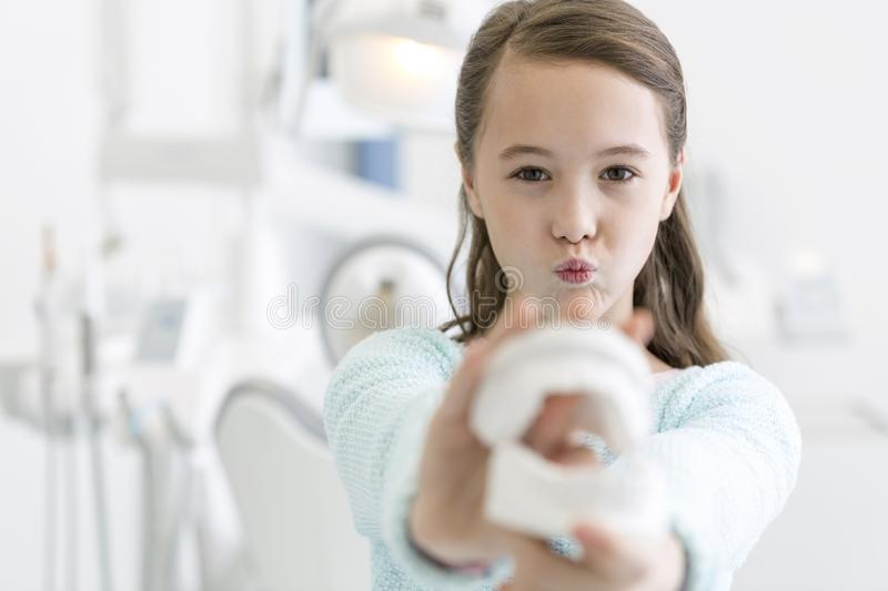 Closeup of girl showing dentures while making face at dental clinic stock photos