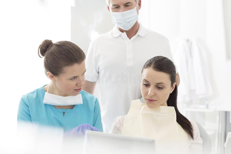 Dentist with assistant explaining procedure to patient at dental clinic stock images