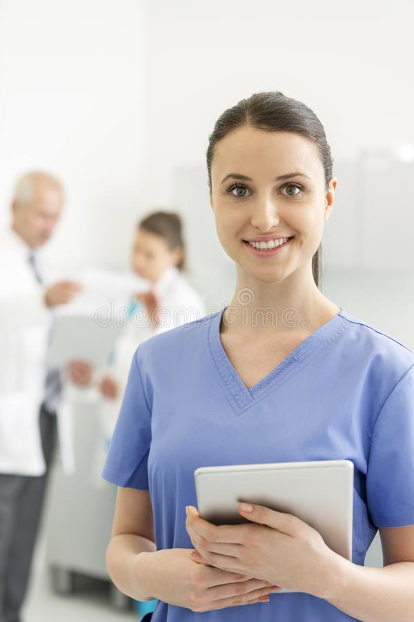 Smiling nurse with digital tablet standing against colleagues at clinic stock image