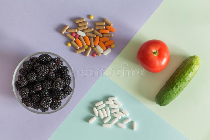 Medical pills and fresh, healthy fruit a source of natural vitamins royalty free stock image