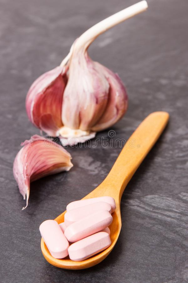 Medical pills on spoon and natural garlic, choice between healthy nutrition and supplements for treatment. Medical pills on wooden spoon and fresh natural garlic stock images