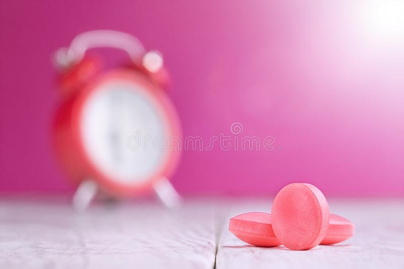 Medical pills on wooden table and clock at background. Medical drug taking times, the schedule of medical treatment royalty free stock images