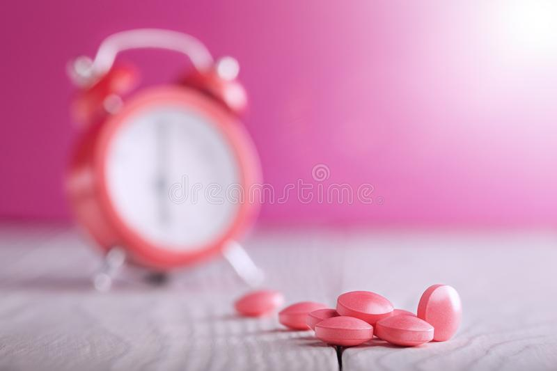 Medical pills on wooden table and clock at background. Medical drug taking times, the schedule of medical treatment. Medical pills on wooden table and clock at royalty free stock photography