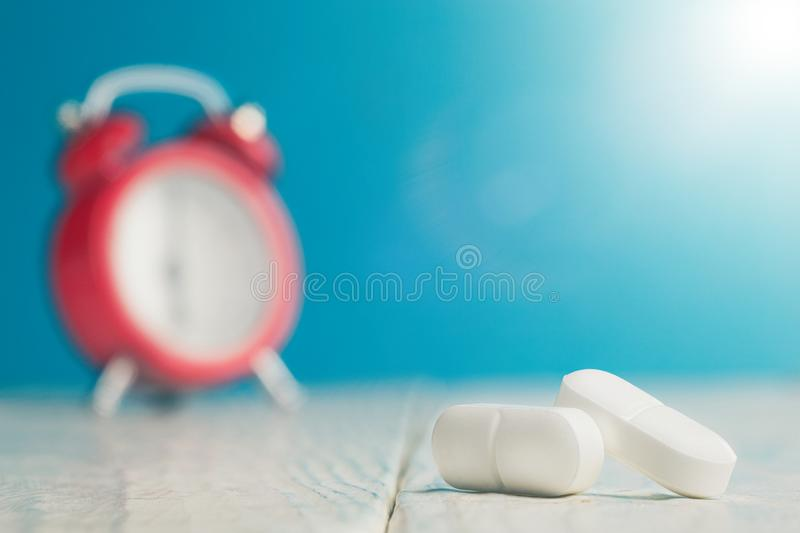 Medical pills on wooden table and clock at background. Medical drug taking times, the schedule of medical treatment. Medical pills on wooden table and clock at stock images