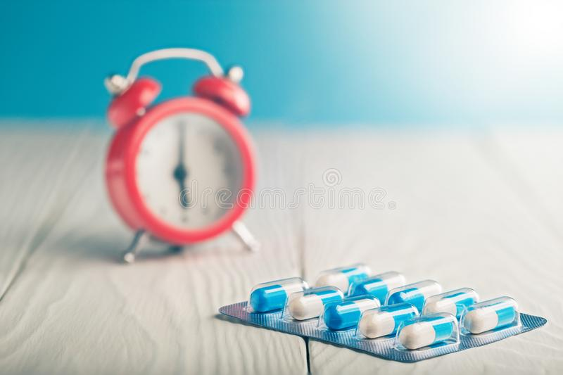 Medical pills on wooden table and clock at background. Medical drug taking times, the schedule of medical treatment. Medical pills on wooden table and clock at royalty free stock image