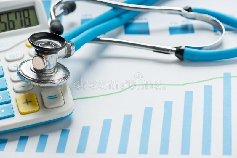 Medical practice financial analysis charts with stethoscope and calculator royalty free stock images