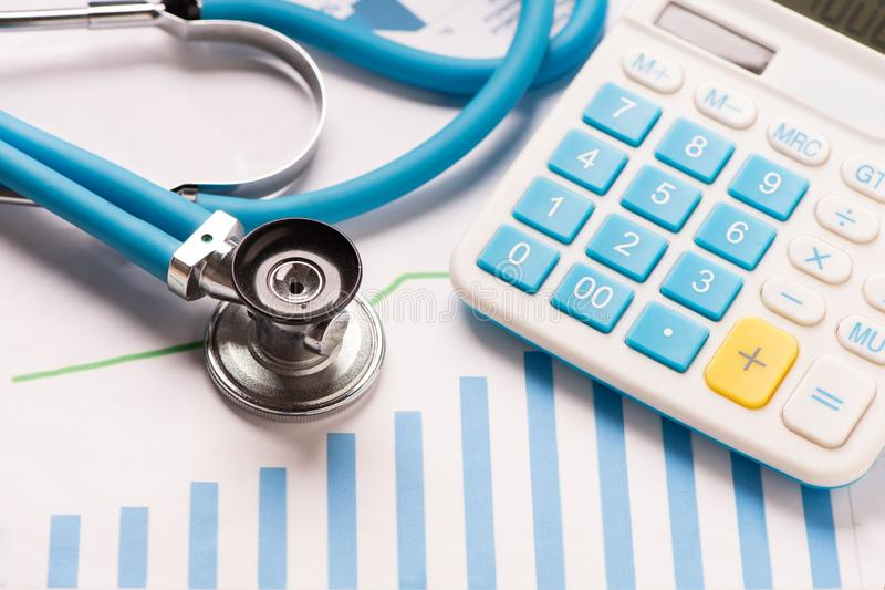 Medical practice financial analysis charts with stethoscope and calculator stock images