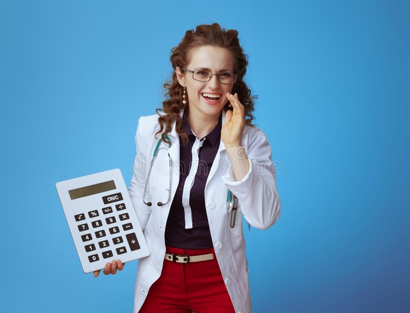 Medical practitioner woman with calculator telling news. Happy elegant medical practitioner woman in bue shirt, red pants and white medical robe with big white royalty free stock photo