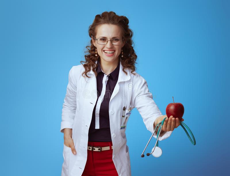 Medical practitioner woman giving stethoscope and red apple. Happy modern medical practitioner woman in bue shirt, red pants and white medical robe giving royalty free stock photo