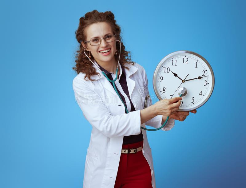 Medical practitioner woman listening with stethoscope clock. Smiling modern medical practitioner woman in bue shirt, red pants and white medical robe listening royalty free stock photo