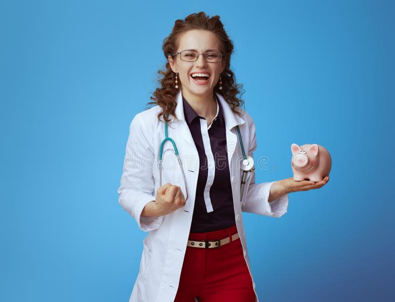 Medical practitioner woman with piggy bank rejoicing on blue. Happy modern medical practitioner woman in bue shirt, red pants and white medical robe with piggy stock photo