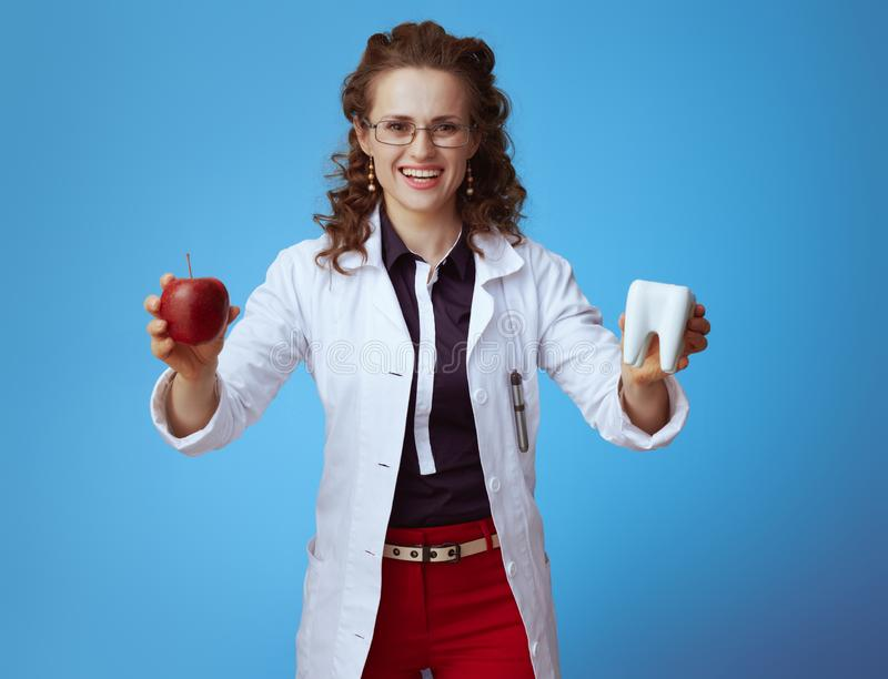 Medical practitioner woman showing red apple and white tooth. Smiling modern medical practitioner woman in bue shirt, red pants and white medical robe showing royalty free stock photography