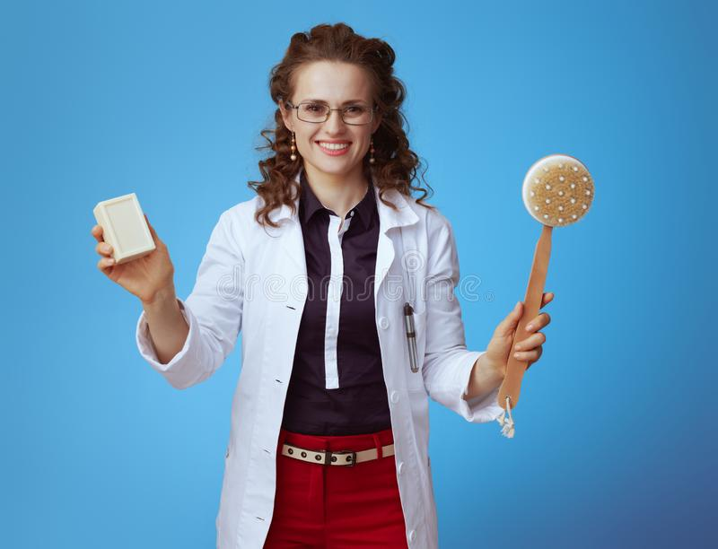 Medical practitioner woman showing soap bar and bath brush. Happy modern medical practitioner woman in bue shirt, red pants and white medical robe showing soap royalty free stock photos
