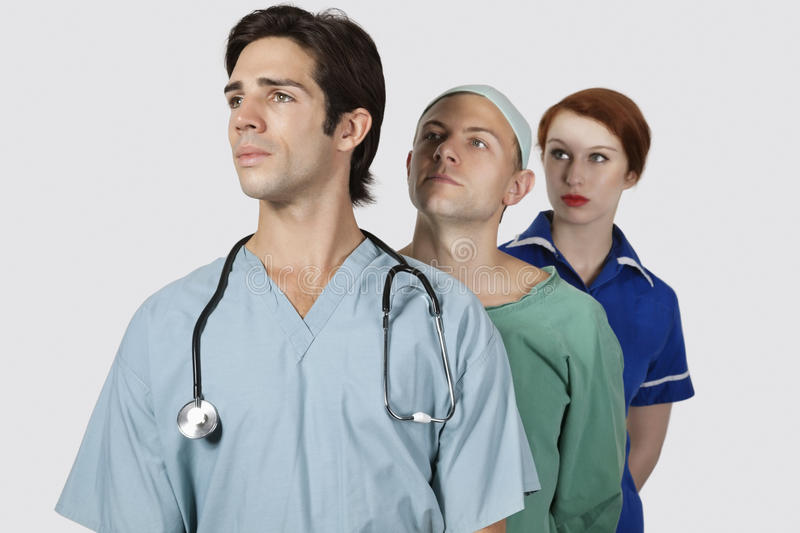 Medical practitioners standing together against gray background royalty free stock photos