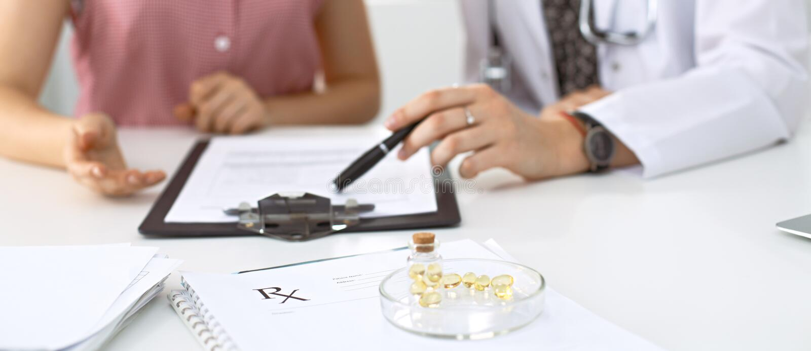 Medical prescription form, capsules and pills are lying against the background of a doctor and patient discussing health royalty free stock photos