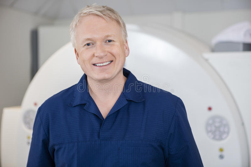 Medical Professional Smiling Against MRI Scanner royalty free stock images