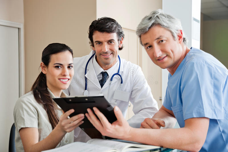 Medical Professionals Standing At Reception. Portrait of multiethnic medical professionals smiling while standing at hospital reception stock photography
