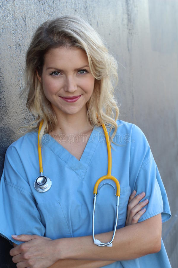 Medical professionals: Woman nurse smiling while working at hospital. Young beautiful blond caucasian female health care worker royalty free stock photography