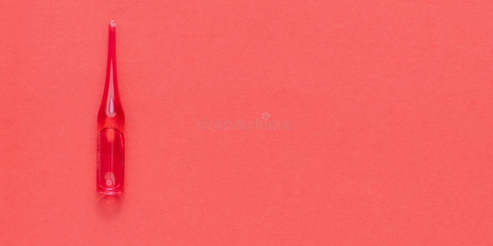 Medical red ampoule on red background. With copy space royalty free stock photo