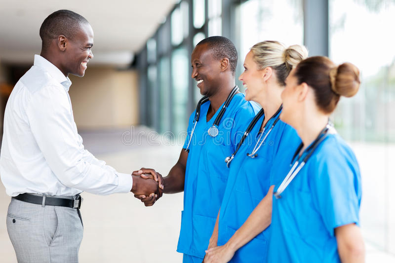 medical rep handshaking doctors stock photo