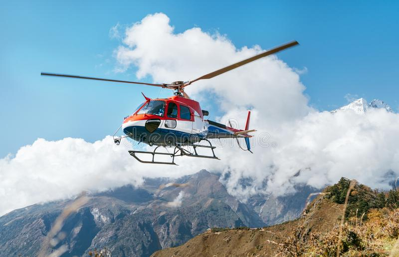 Medical Rescue helicopter landing in high altitude Himalayas mountains. Safety and travel insurance concept image stock photos