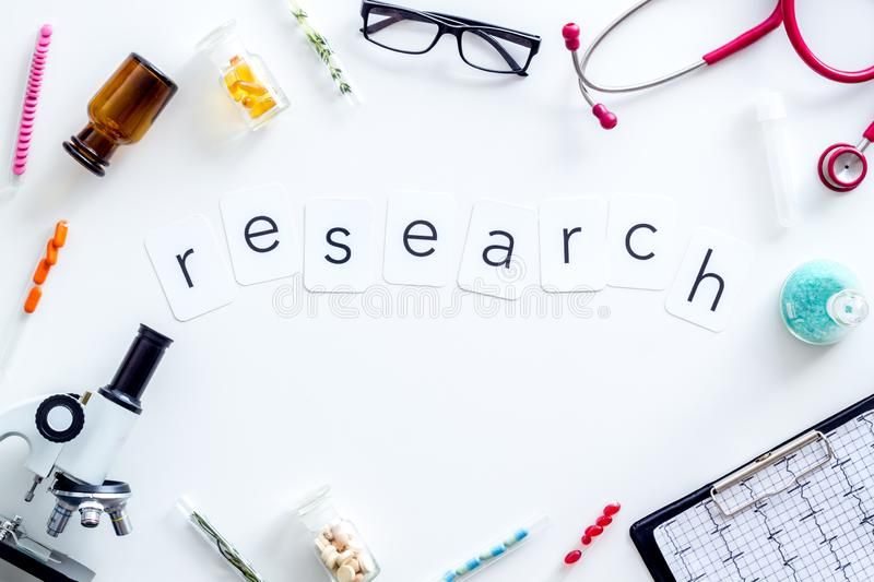 Medical research concept with microscope, stethoscope, cardiogram, test tube frame on white background top view. Desk of doctor in laboratory. Medical research stock photo