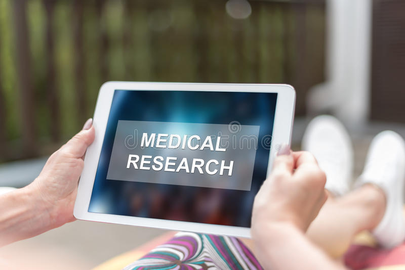 Medical research concept on a tablet. Female hands holding a tablet with medical research concept royalty free stock photography