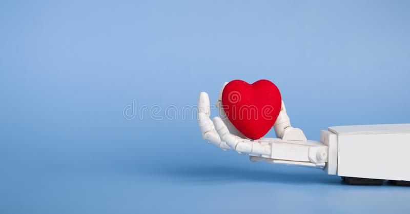 Medical robotics and science fiction concept. Robot hand holding red heart royalty free stock image