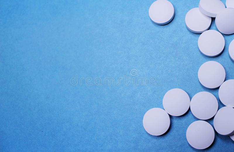 Medical round white tablets, calcium vitamins closeup on blue background with space for text or image. Pills. stock images