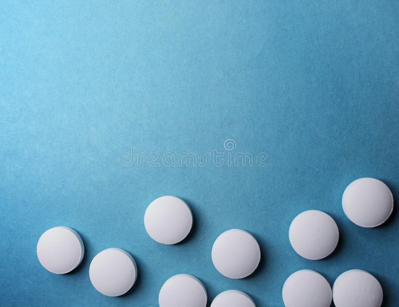 Medical round white tablets, calcium vitamins closeup on blue background with space for text or image. Pills. stock image